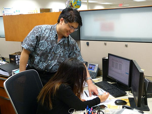 manager helping employee at desk